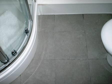 Before Picture - Grout Colour restored on a Ceramic Tiled Bathroom Floor by the Tile Doctor